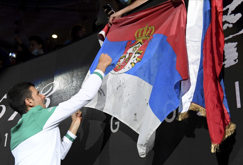 Serbia's Novak Djokovic signs autographs after defeating Russia's Daniil Medvedev during the men's singles final at the Australian Open tennis champio...