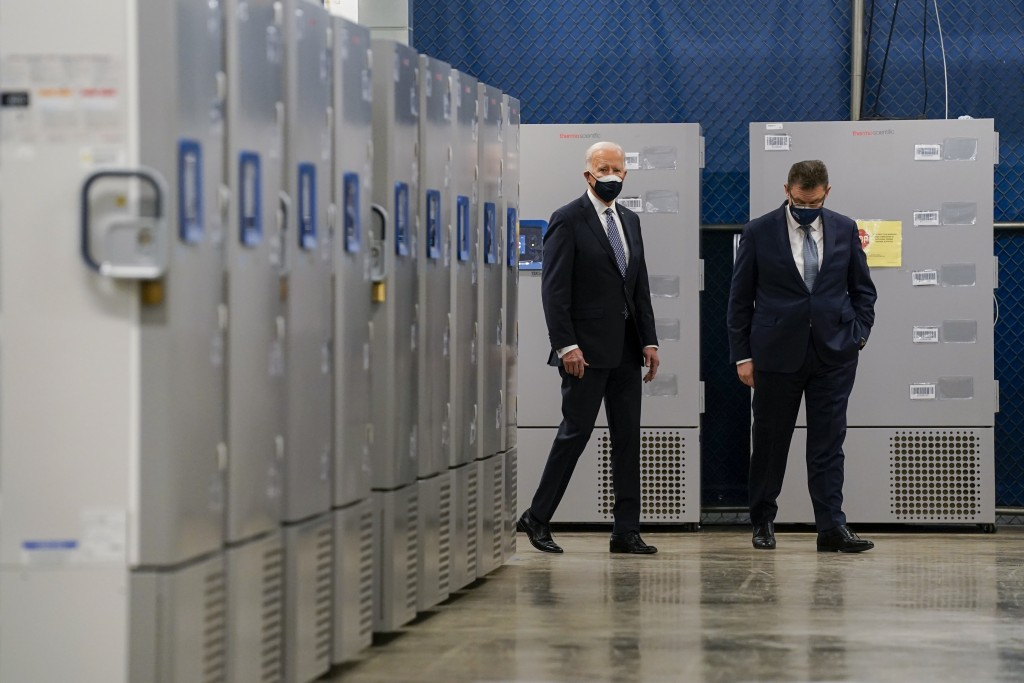 FILE - In this Feb. 19, 2021, file photo President Joe Biden walks by freezers used to hold the Pfizer COVID-19 vaccine as he tours a Pfizer manufactu...
