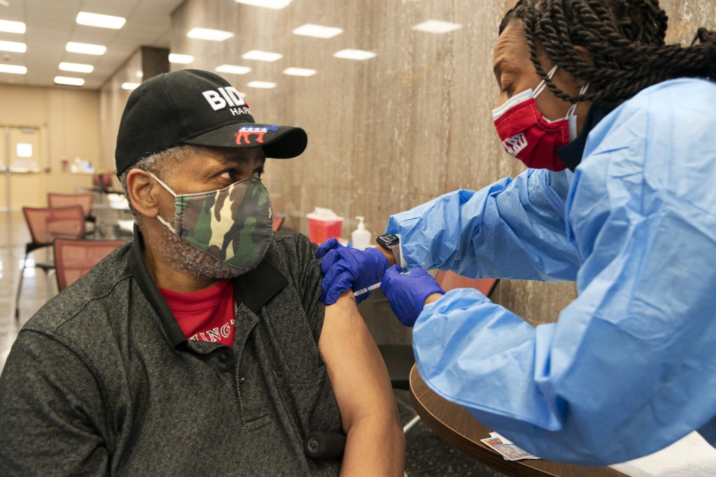 In this Thursday, Feb. 11, 2021, photo Reginald Henry, 69, of Washington, receives his second dose of the COVID-19 vaccine at a clinic at Howard Unive...