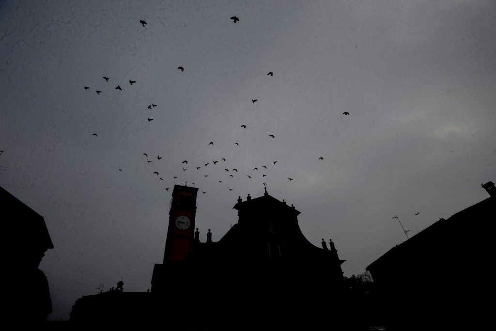 Birds fly over the San Biagio church in Codogno, northern Italy, Sunday, Feb. 21, 2021. Italians are marking one year since their country experienced ...