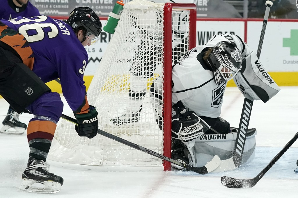Los Angeles Kings goaltender Calvin Petersen, right, makes a save on a shot from Arizona Coyotes right wing Christian Fischer (36) during the first pe...