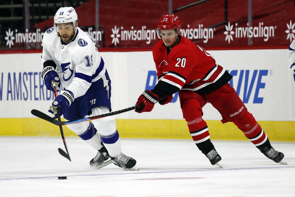 Carolina Hurricanes Sebastian Aho (20) tries to remove Tampa Bay Lightning's Barclay Goodrow (19) from the puck during the second period of an NHL hoc...
