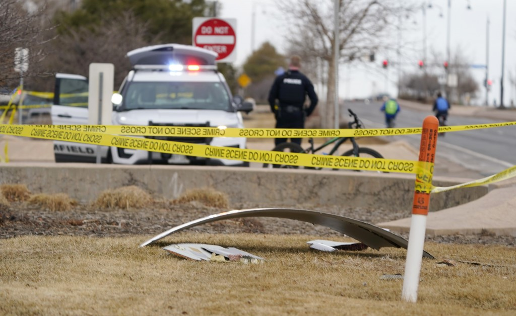 A piece of commercial airplane debris is surrounded by police tape where it landed along Midway Boulevard in Broomfield, Colo., as the plane shed part...