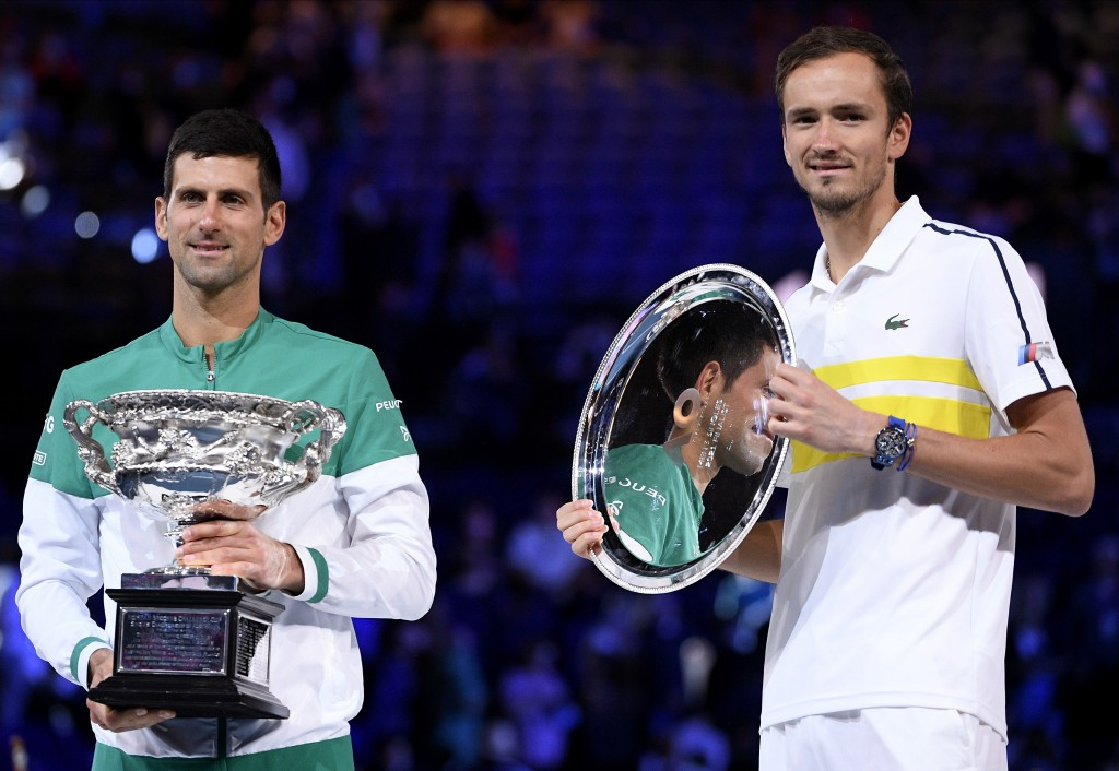 Serbia's Novak Djokovic, left, holds the Norman Brookes Challenge Cup after defeating Russia's Daniil Medvedev, right, in the men's singles final at t...