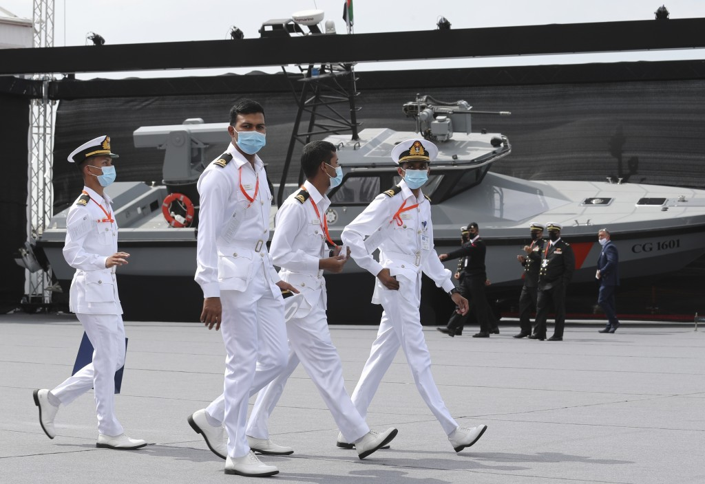 Navy officers walk past a combat boat built by Alfattan in the UAE, on the opening day of the regions leading naval defence and maritime security even...