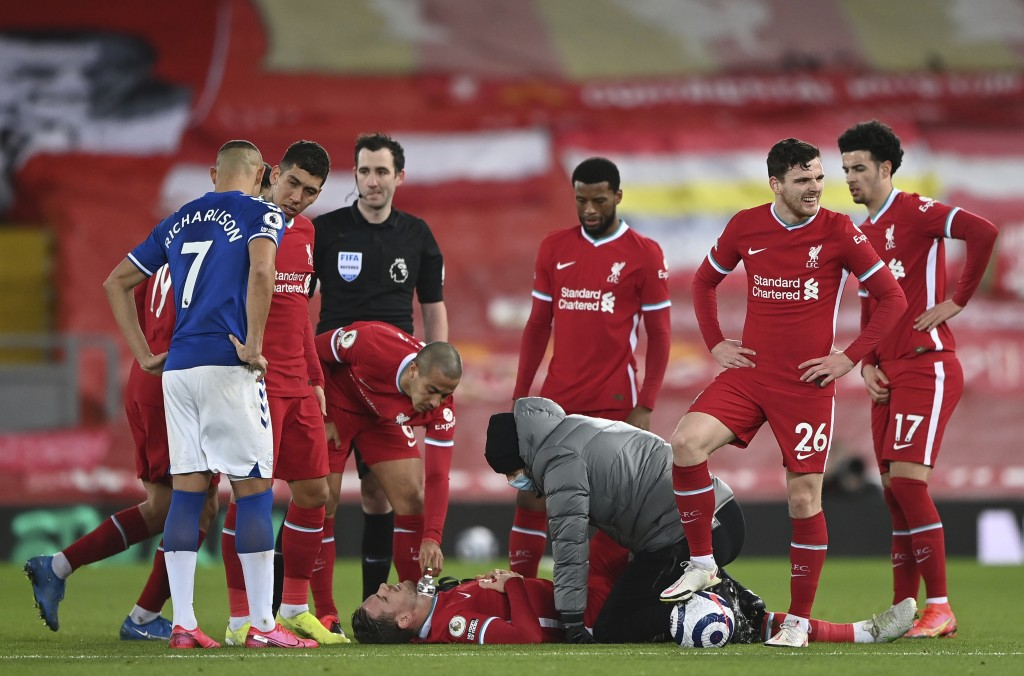Liverpool's Jordan Henderson lies injured on the ground and is attended to by a member of the Liverpool medical team during the English Premier League...