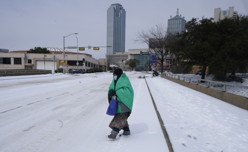 FILE - In this Feb. 16, 2021, file photo, a woman wrapped in a blanket crosses the street near downtown Dallas. As temperatures plunged and snow and i...
