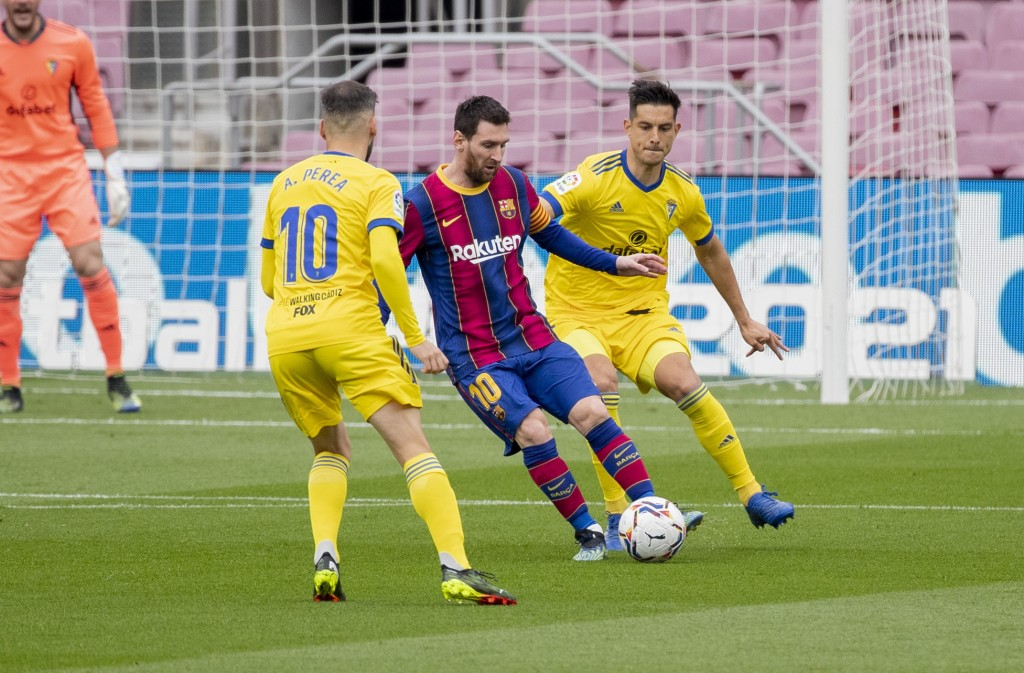 Barcelona's Lionel Messi, center, controls the ball with Cadiz's Marcos Mauro during the Spanish La Liga soccer match between FC Barcelona and Cadiz a...