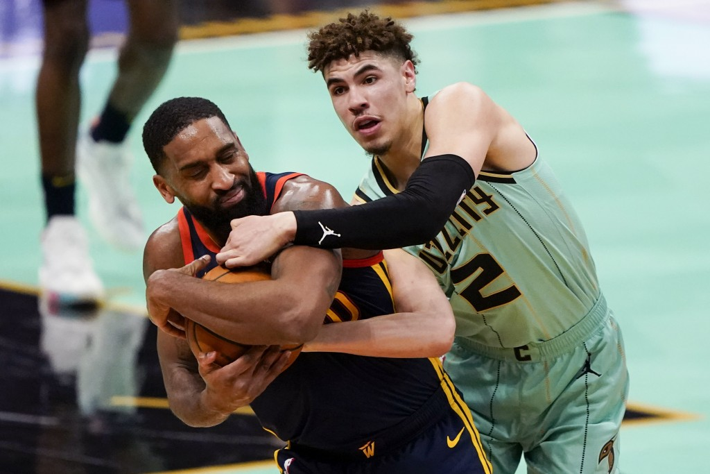 Golden State Warriors guard Brad Wanamaker, left, and Charlotte Hornets guard LaMelo Ball battle for the ball during the second half of an NBA basketb...