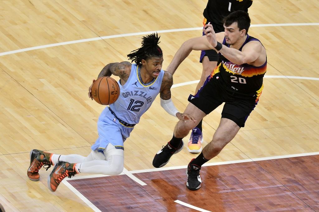 Memphis Grizzlies guard Ja Morant (12) drives against Phoenix Suns forward Dario Saric (20) in the second half of an NBA basketball game Saturday, Feb...