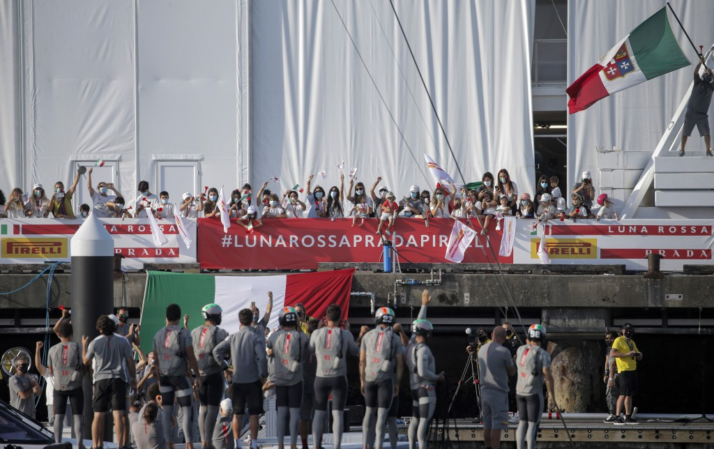 Supporters of Italy's Luna Rossa team wave as they celebrate after defeating Britain's INEOS Team UK in race eight of the Prada Cup on Auckland's Wait...