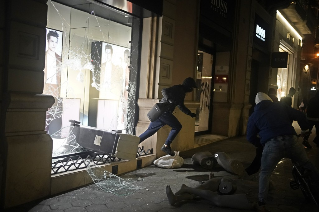 A person carrying goods runs from a smashed shop window during a protest condemning the arrest of rap singer Pablo Hasél in Barcelona, Spain, Saturday...