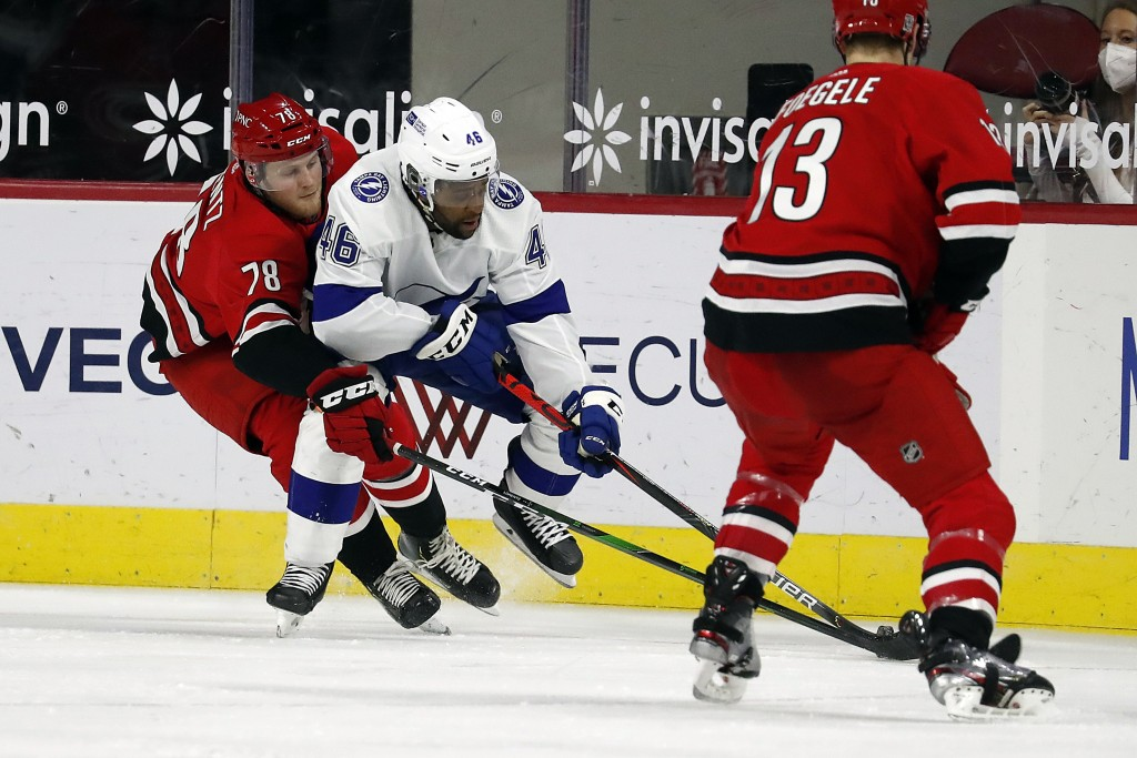Carolina Hurricanes' Steven Lorentz (78) reaches around Tampa Bay Lightning's Gemel Smith (46) to tip the puck away during the second period of an NHL...