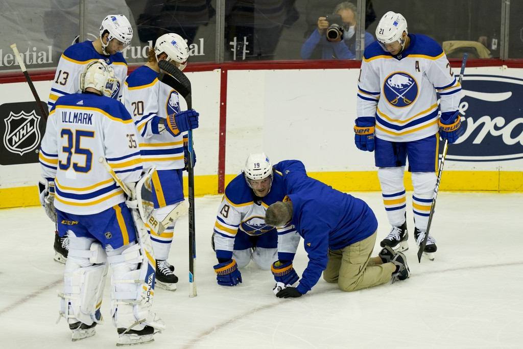 Buffalo Sabres defenseman Jake McCabe (19) reacts after taking an injury and being helped off the ice during the third period of an NHL hockey game ag...