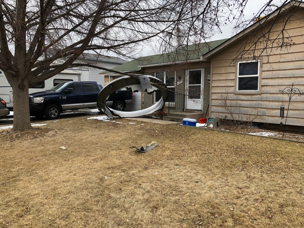 In this photo provided by the Broomfield Police Department on Twitter, debris is scattered in the front yard of a house at near 13th and Elmwood, Satu...