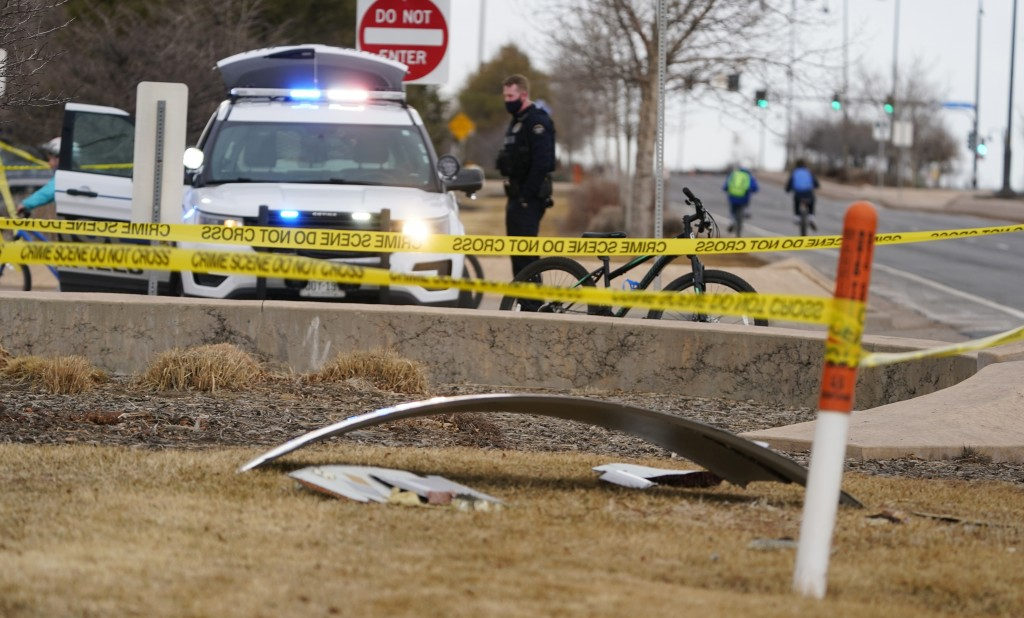 A piece of debris from a commercial airplane is marked off by police tape where it landed along Midway Boulevard in Broomfield, Colo., as the plane sh...