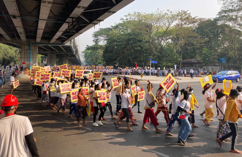 Anti-coup protesters holding posters of deposed Myanmar leader Aung San Suu Kyi march outside the Hledan Centre in Yangon, Myanmar, Sunday, Feb. 21, 2...