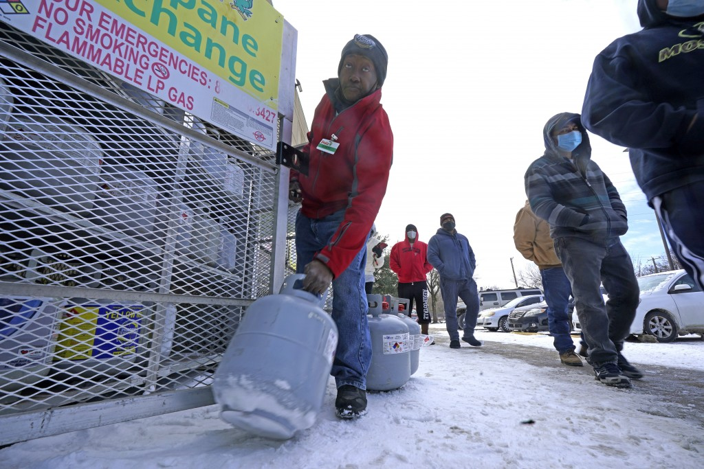 FILE - In this Feb. 16, 2021, file photo, Robert Webster pulls a full canister of propane for sale as customers line up to enter a grocery store in Da...