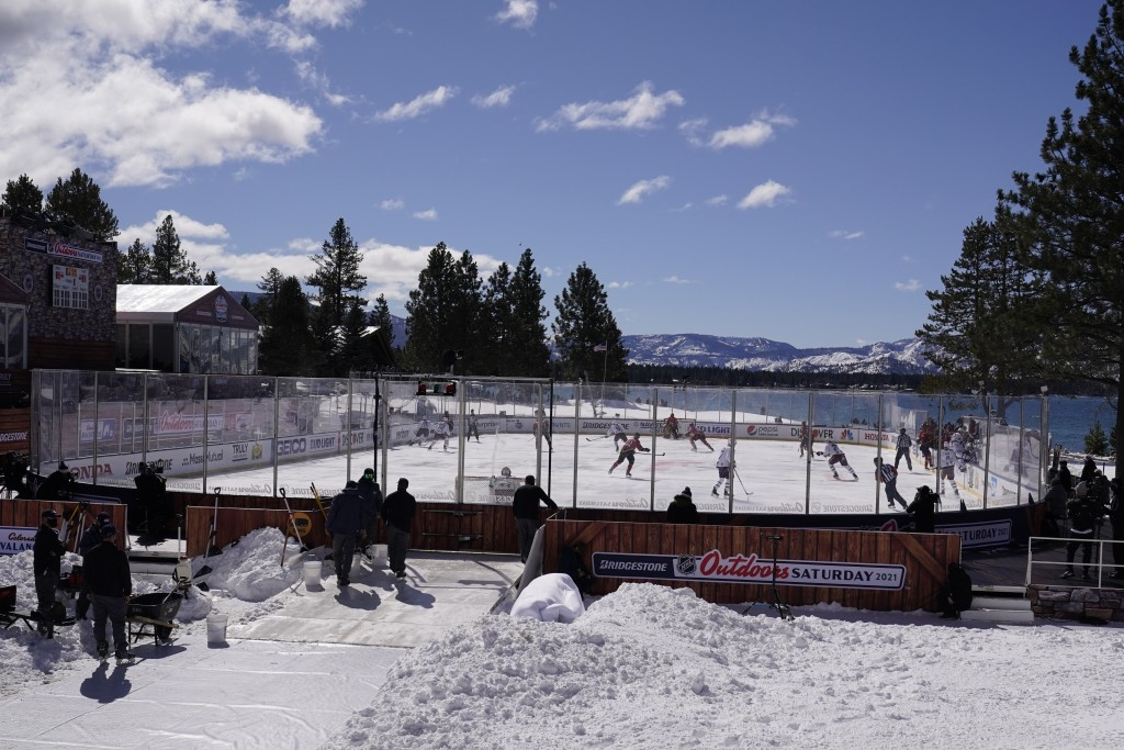 Members of the Colorado Avalanche, in white, and the Vegas Golden Knights, red, play during the first period of the Outdoor Lake Tahoe NHL hockey game...