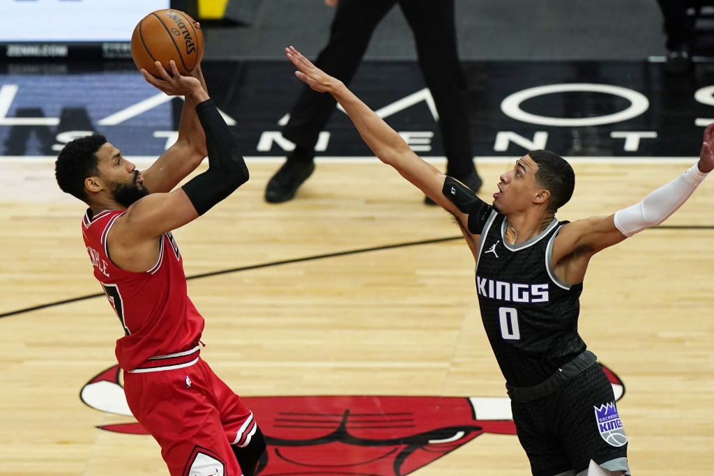 Chicago Bulls guard Garrett Temple, left, shoots against Sacramento Kings guard Tyrese Haliburton during the first half of an NBA basketball game in C...