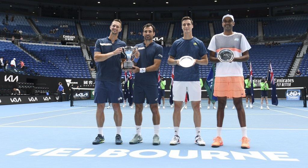Slovakia's Filip Polasek, left, and Croatia's Ivan Dodig, second left, pose with their trophy after defeating Rajeev Ram, right, of the US and Britain...