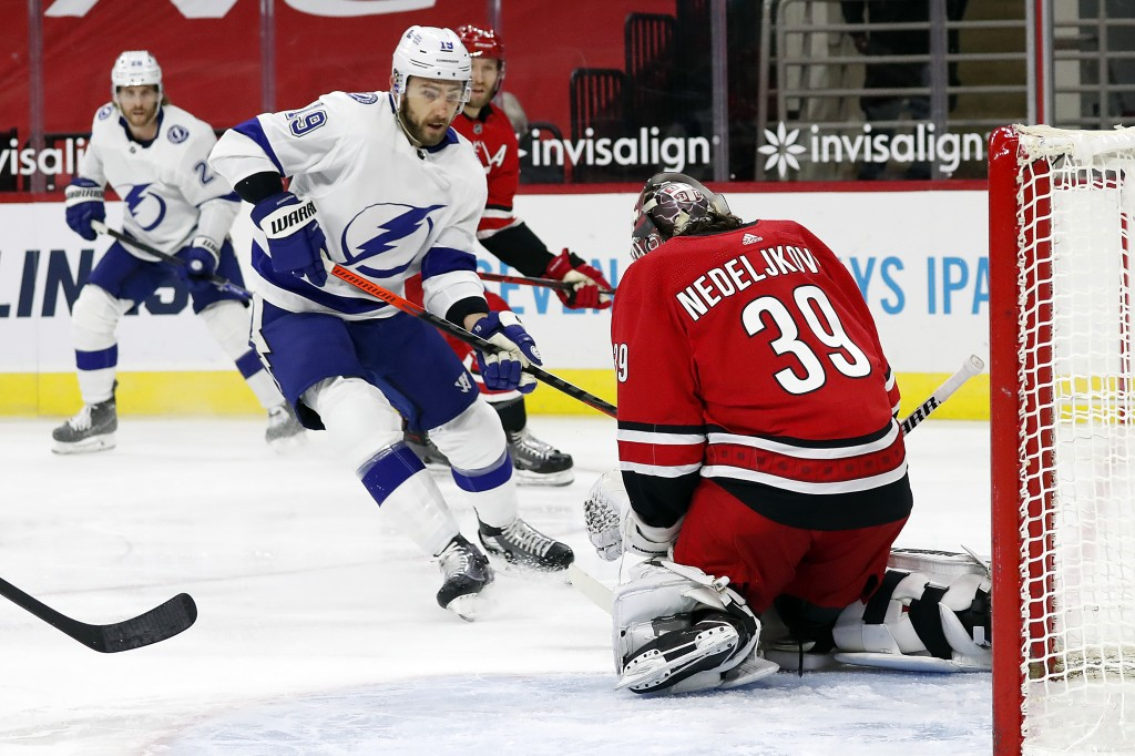 Tampa Bay Lightning's Barclay Goodrow (19) has the puck swallowed by Carolina Hurricanes goaltender Alex Nedeljkovic (39) during the first period of a...