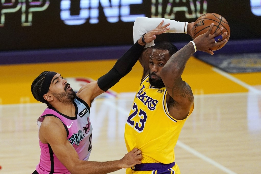 Los Angeles Lakers forward LeBron James, right, tries to pass as Miami Heat guard Gabe Vincent defends during the first half of an NBA basketball game...