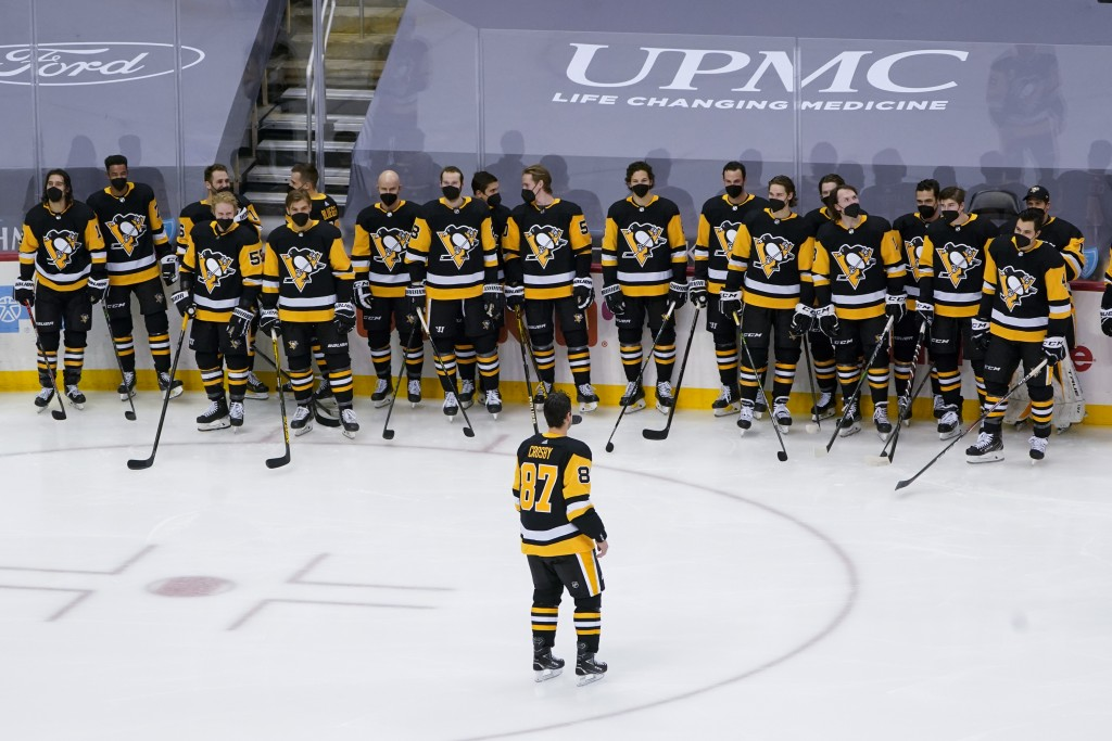 Pittsburgh Penguins' Sidney Crosby, foreground, skates back to teammates during a ceremony honoring his 1000th NHL hockey game with the team before an...