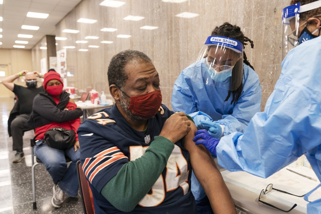 In this Thursday, Feb. 11, 2021, photo Peter Thomas, 58, of Washington, receives his second dose of the COVID-19 vaccine at a clinic at Howard Univers...