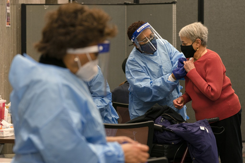In this Thursday, Feb. 11, 2021, photo Charlotte Lee, 78, of Washington, right, prepares to receive her second dose of the COVID-19 vaccine at a clini...
