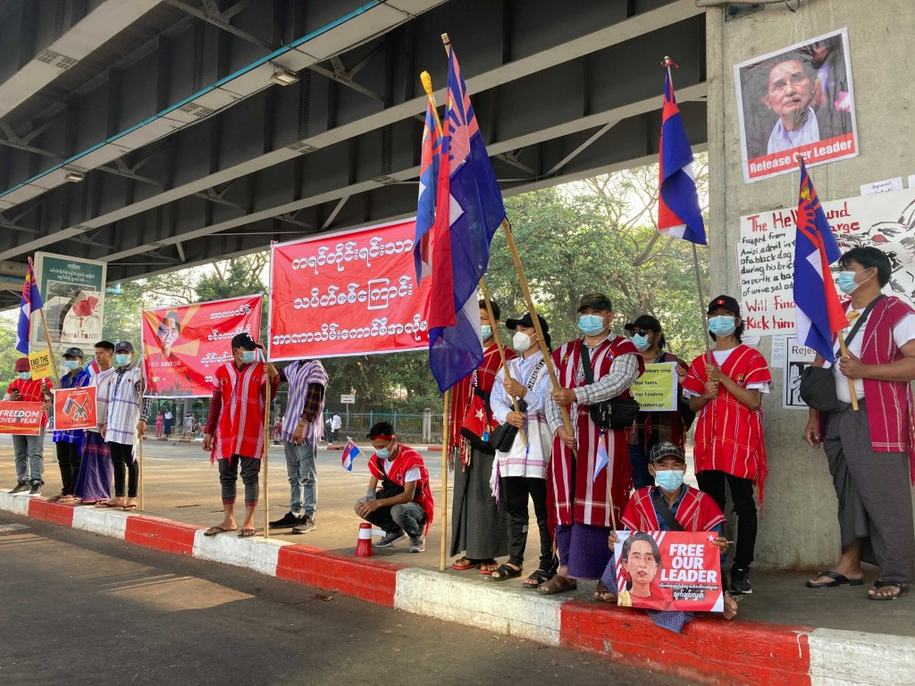 """Anti-coup protesters hold a banner that reads, """"Karen National Group! Don't want military dictatorship,"""" during a silents protest outside the Hledan C..."""