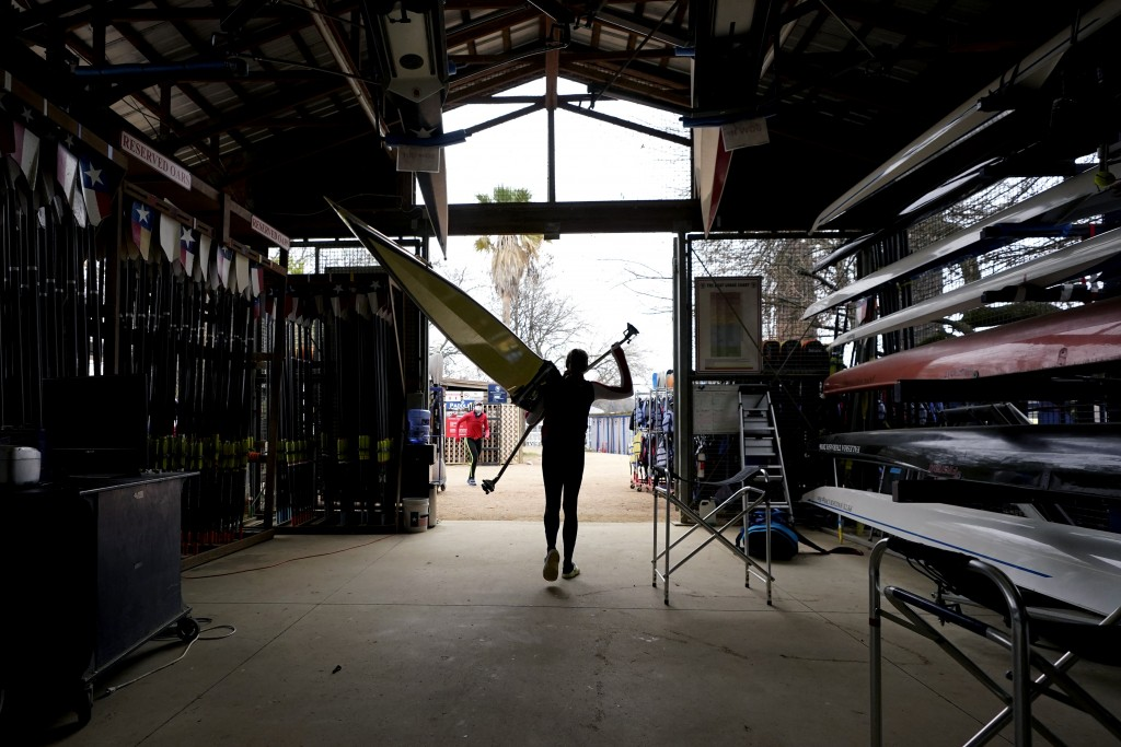 Rower Gevvie Stone carries her board before training at Lady Bird Lake ahead of the upcoming U.S. Olympic rowing trials, Friday, Feb. 12, 2021, in Aus...