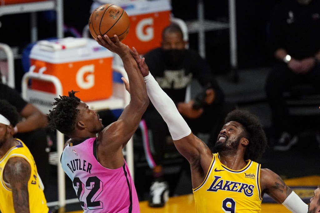 Miami Heat forward Jimmy Butler, left, shoots as Los Angeles Lakers guard Wesley Matthews defends during the first half of an NBA basketball game Satu...
