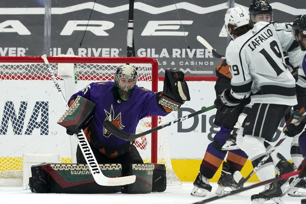 Arizona Coyotes goaltender Darcy Kuemper, left, makes a glove-save as Los Angeles Kings right wing Alex Iafallo (19) and Coyotes defenseman Ilya Lyubu...