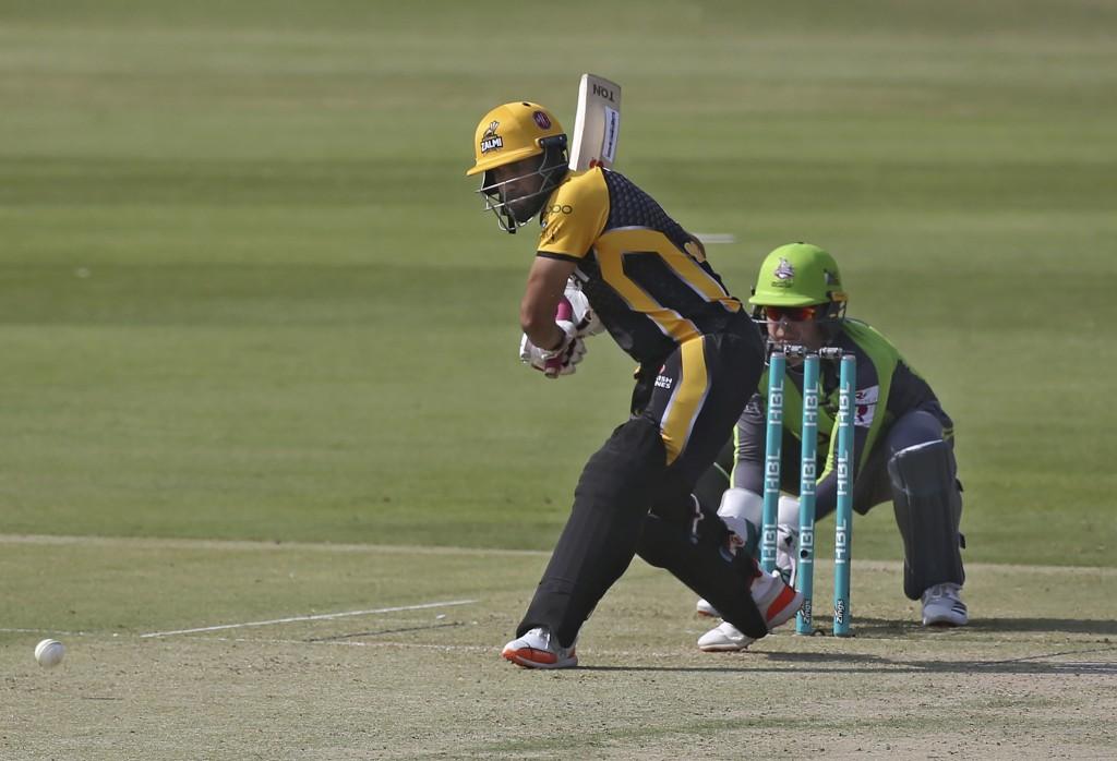 Peshawar Zalmi Ravi Bopara, left, plays a shot while Lahore Qalandars wicketkeeper Ben Dunk watches during a Pakistan Super League T20 cricket match b...