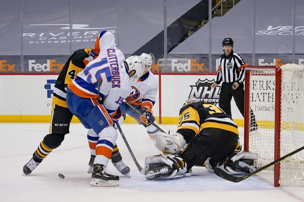 The puck is under New York Islanders' Cal Clutterbuck (15) and Pittsburgh Penguins' Cody Ceci (4) as they battle in front of Penguins goaltender Trist...