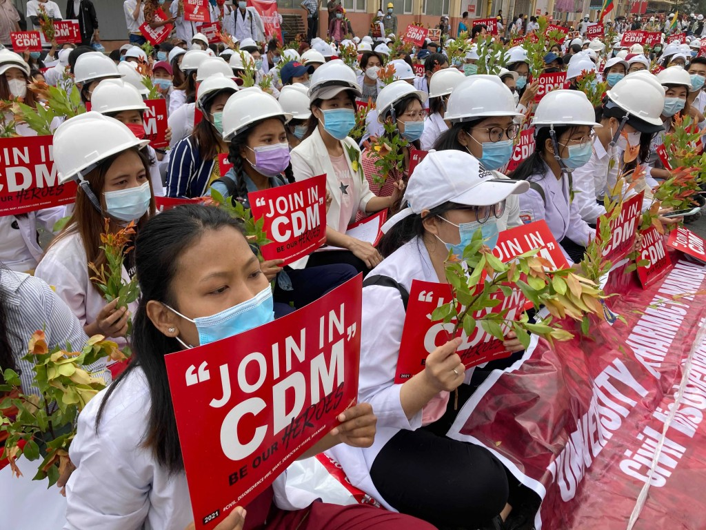 Medical students wearing face masks hold placards as they gather during an anti-coup protest in Mandalay, Myanmar, Sunday, Feb. 21, 2021. Riot police ...