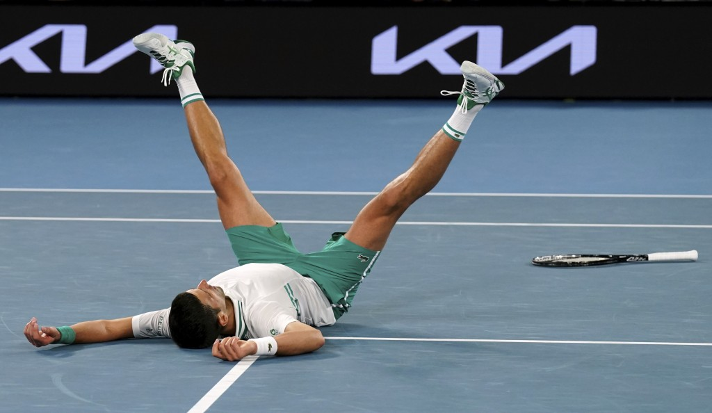 Serbia's Novak Djokovic falls as he celebrates after defeating Russia's Daniil Medvedev in the men's singles final at the Australian Open tennis champ...