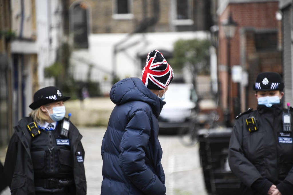A member of the public wearing a Union Flag themed hat walks past the side entrance of the King Edward VII Hospital in London, Sunday, Feb. 21, 2021. ...