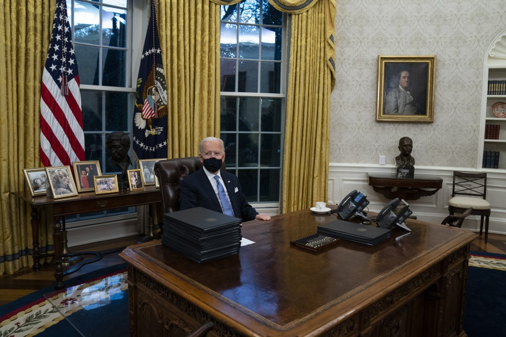 President Joe Biden signs a series of executive orders in the Oval Office of the White House, Wednesday, Jan. 20, 2021, in Washington. (AP Photo/Evan ...