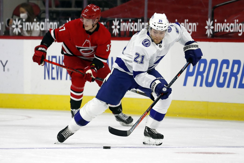 Tampa Bay Lightning's Brayden Point (21) skates with the puck after taking it away from Carolina Hurricanes' Andrei Svechnikov (37) during the first p...