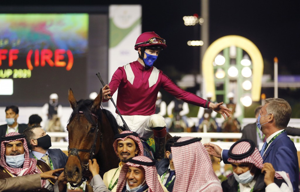 Irish jockey David Egan celebrates as rides his horse Mishriff after reaching the finish point of the final race of the $20 million, the Saudi Cup, at...