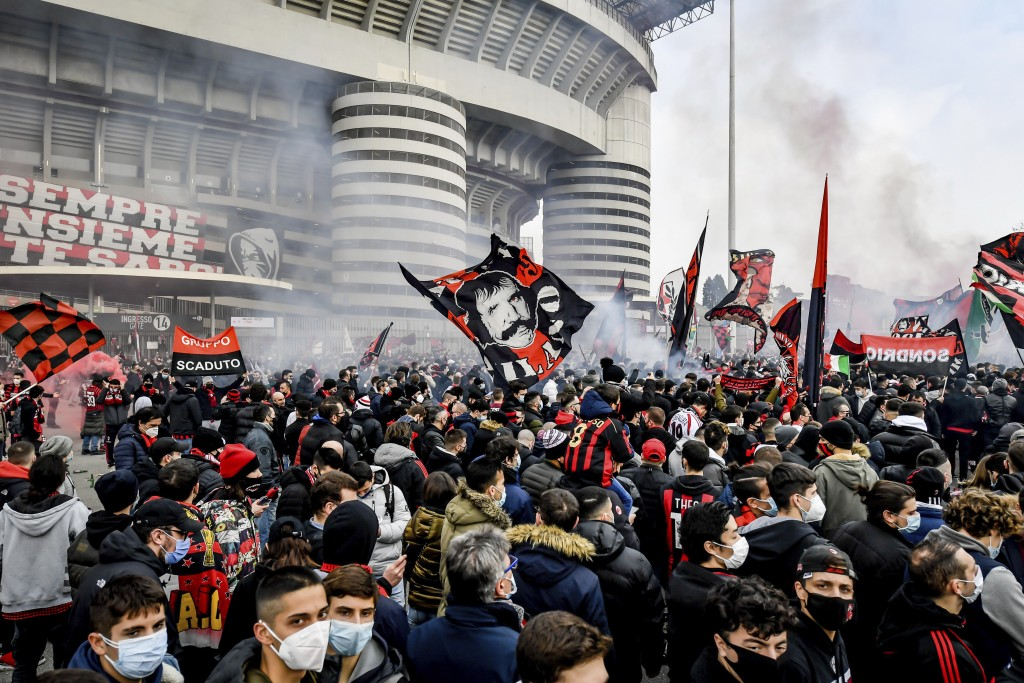 AC Milan supporters wave flags and light flares outside the San Siro Stadium in Milan, Italy, Sunday, Feb. 21, 2021 prior to to the Serie A soccer mat...