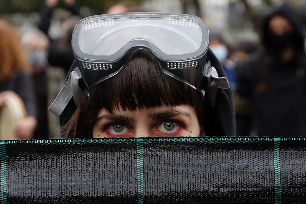 A protestor with a diving mask on her head, holds a banner during a protest in the capital Nicosia, on Saturday, Feb. 20, 2021, against the corruption...