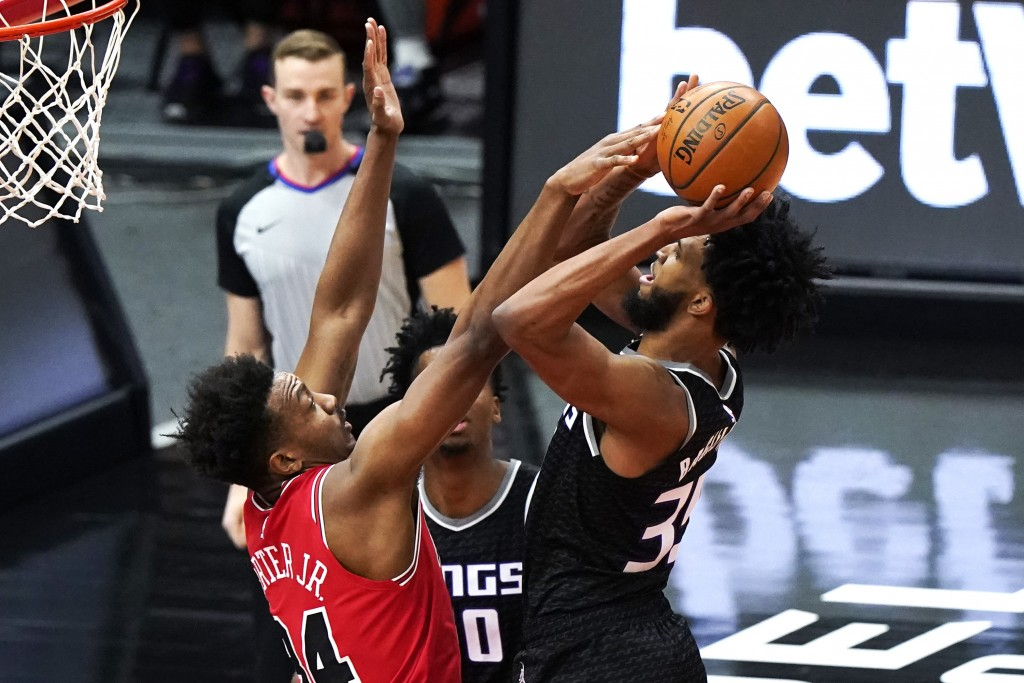 Sacramento Kings forward Marvin Bagley III, right, shoots against Chicago Bulls center Wendell Carter Jr., during the first half of an NBA basketball ...