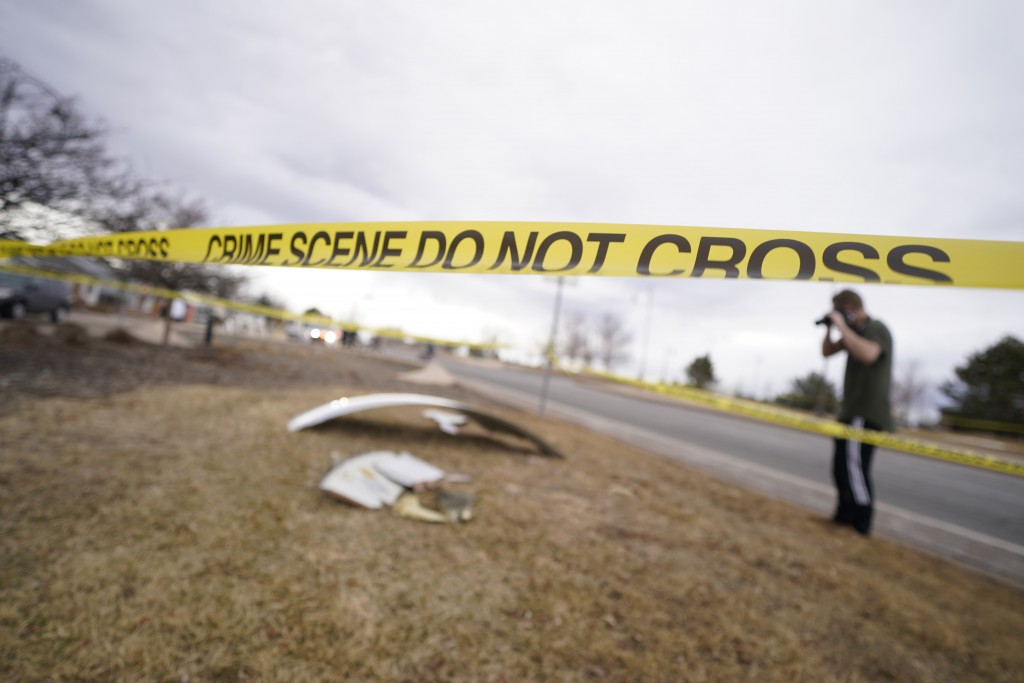 People look over debris that fell off a plane that shed parts over a neighborhood in Broomfield, Colo., Saturday, Feb. 20, 2021. The plane was making ...