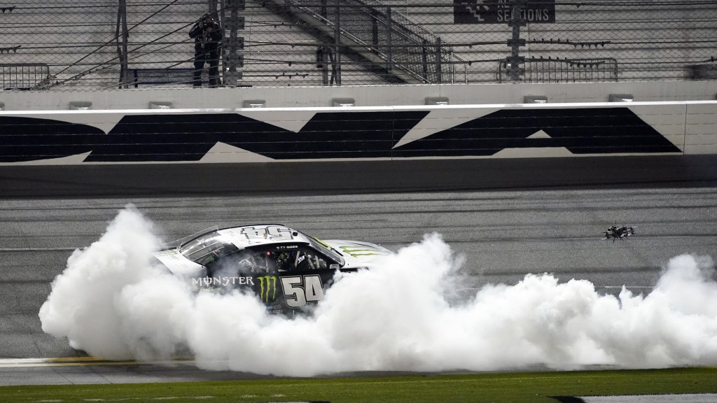 Ty Gibbs (54) celebrates with a burnout in front of the grandstands after winning the NASCAR Xfinity Series road course auto race at Daytona Internati...