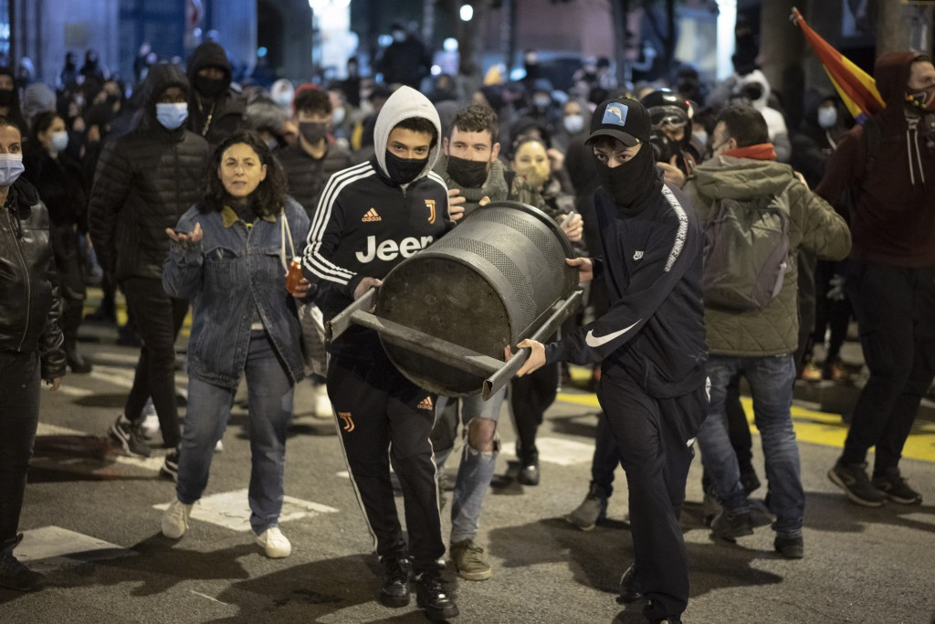 Demonstrators carry a rubbish bin to throw towards police officers protecting a national police station during clashes following a protest condemning ...