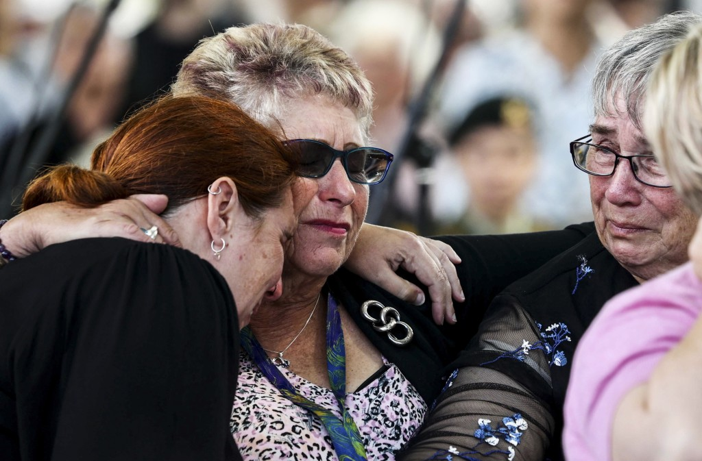 Women embrace as they attend the 10th anniversary memorial service of the 2011 Christchurch earthquake in Christchurch, New Zealand, Monday, Feb. 22, ...