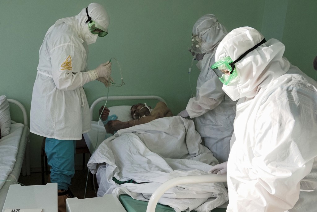 Medical workers treat a coronavirus patient in a COVID-19 unit of a hospital in Sortavala, Karelia region, Russia, Tuesday, Feb. 16, 2021. Russia's ro...